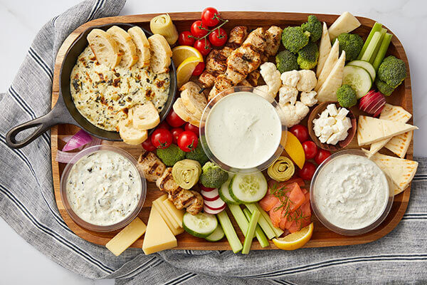 A platter of vegetables, crackers, and dairy based dips