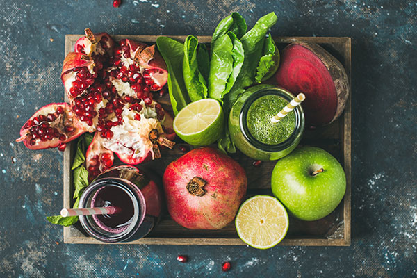 Juices and fruits in a basket from above