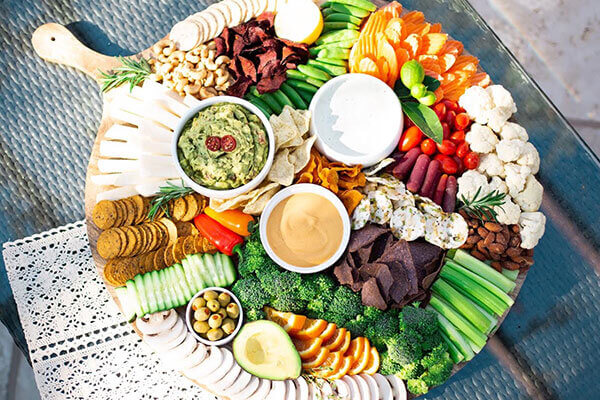 A platter of vegetables, crackers, and plant based dips